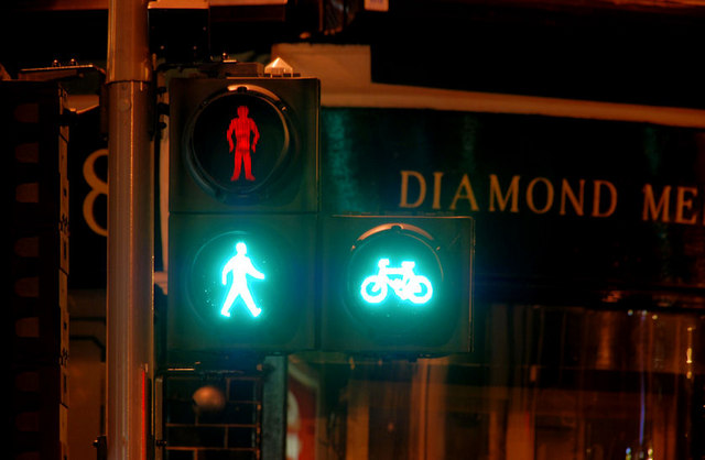 Streetlight with stick figures and bikes