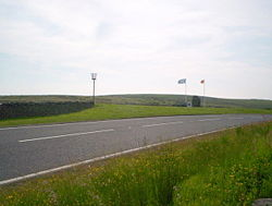 The A68 at Carter Bar with border flags, marker stone and beacon - Geograph - 1383678.jpg